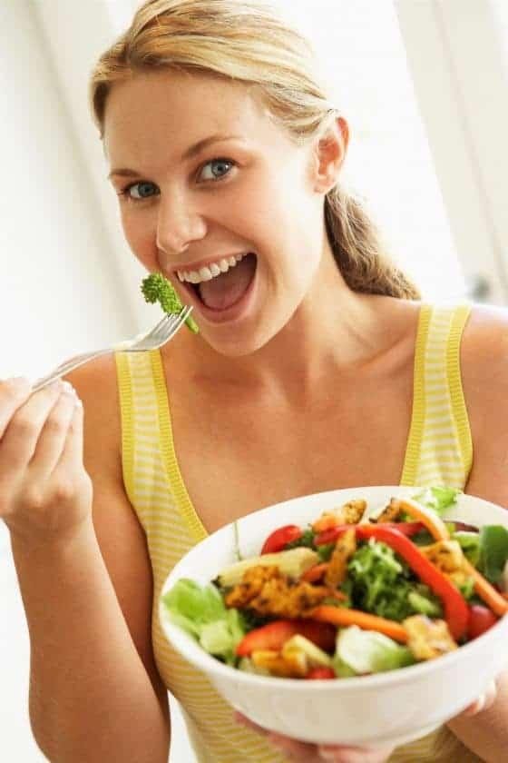 Bela mulher loira de blusa amarela com a sua salada pronta pra comer um brócolis